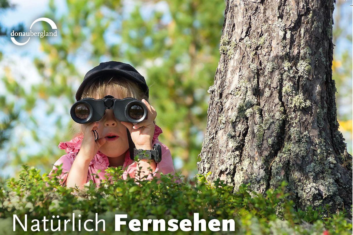 Text: Natürlich Fernsehen; Kind versteckt sich und schaut durch ein Fernglasd