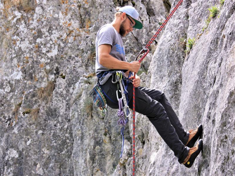 Man Klettert mit Sicherung an einer Felswand