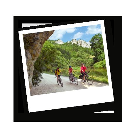 Drei Personen fahren nebeneinander auf einen Kiesweg mit dem Fahrrad durch das Donautal